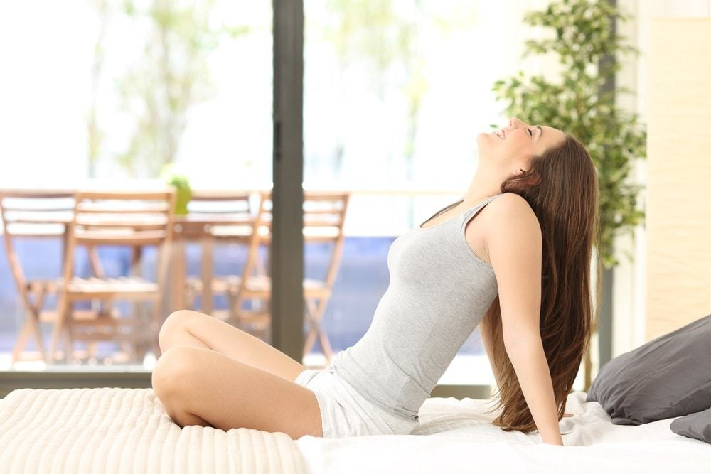 Side view of a woman breathing and sitting on a bed in an hotel room or home with a window in the background