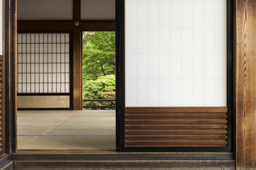 View into a japanese room with open shoji door and green garden in the background
