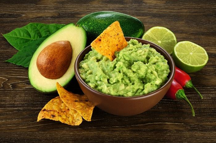 Guacamole nachos and guacamole ingredients on dark wooden background