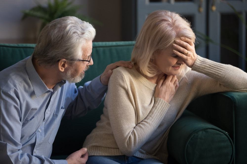 Grey haired husband helping overcome problem, supporting unhappy mature wife at home