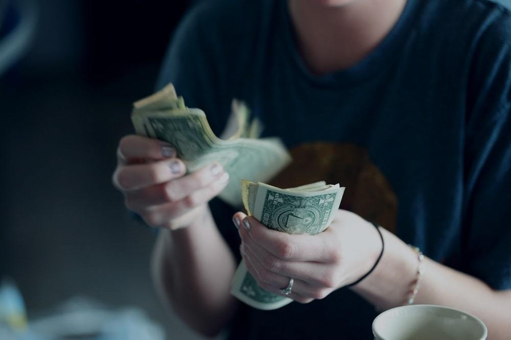 A twenty-four year old woman counting dollar bills